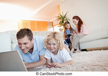 Father and son with laptop on the floor