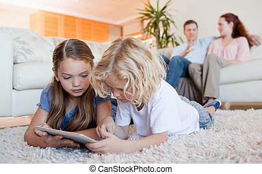 Siblings using tablet on the living room floor - Siblings...