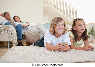 Siblings lying on the carpet watching tv