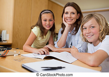 Mother doing homework with children