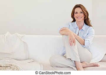 Smiling mature woman sitting on sofa - Smiling mature woman...