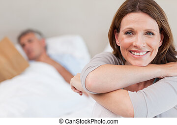 Smiling woman on bed with reading husband in the background...