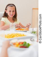 Happy girl having dinner at dinner table