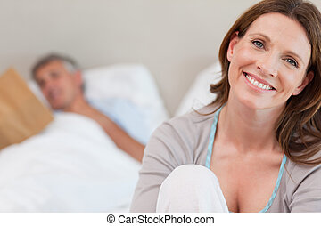 Smiling mature woman on bed with reading husband behind her...