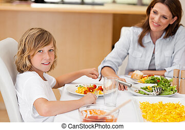 Side view of boy sitting at the dinner table - Side view of...