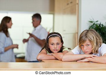 Sad looking siblings with fighting parents behind them - Sad...