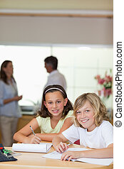 Children doing homework with their parents behind them