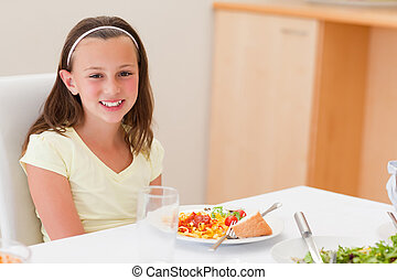 Smiling girl with dinner at the table