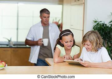 Children using tablet in the kitchen with father behind them...