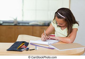 Girl doing homework in the kitchen