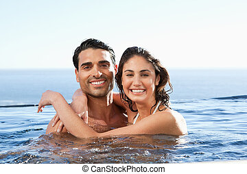 Smiling couple embracing in the pool - Smiling young couple...