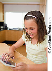Girl using tablet at the kitchen table - Little girl using...