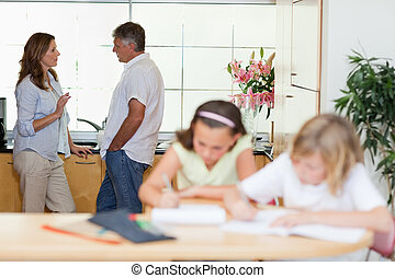 Parents talking with children doing homework in front of...