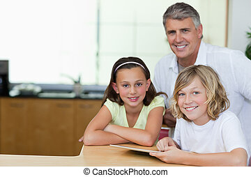 Smiling man with children and tablet in the kitchen -...