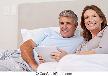 Couple with tablet in bed
