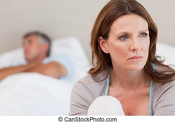 Sad woman on bed with her husband in the background - Sad...