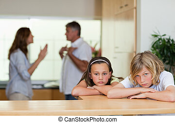 Sad looking siblings with arguing parents behind them - Sad...