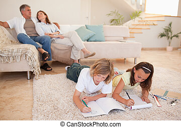 Siblings doing homework on the floor with parents behind...