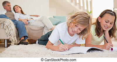 Siblings doing their homework on the carpet with their...
