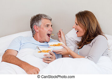 Mature couple eating cereals in bed - Mature couple eating...