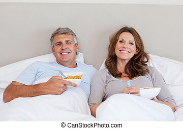 Couple eating cereals in bed - Mature couple eating cereals...