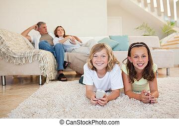 Siblings on the floor watching tv