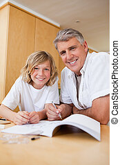 Boy getting help with homework from father