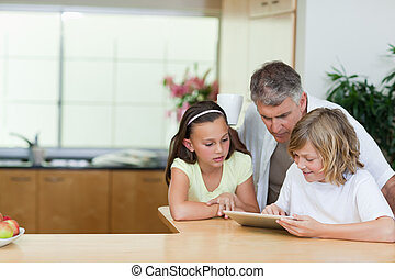 Man looking at tablet his children are using - Man looking...
