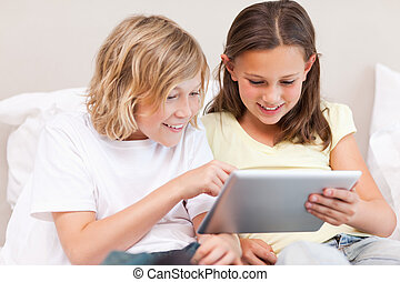 Siblings using tablet on sofa