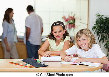 Siblings doing homework with their parents behind them