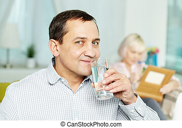 Drinking water - Portrait of happy senior man drinking water...