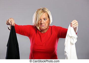 Dirty clothes - A portrait of a mature woman holding dirty...