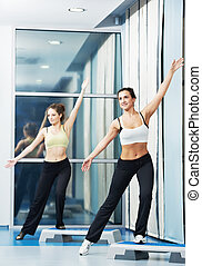 women at aerobics exercise with fitness step board - two...