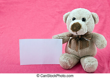 teddy bear with white notice on pink background