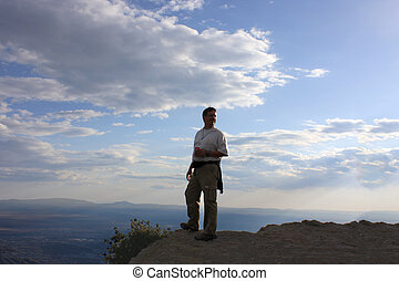 Man is standing on a summit looking backwards