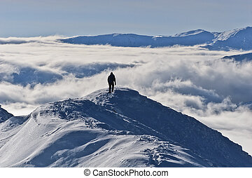 climbing the mountain in winter - climber on the mountain in...