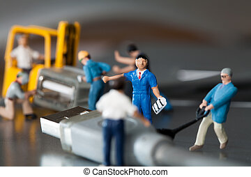 Teamwork In The Workplace. A team of miniature toy model...