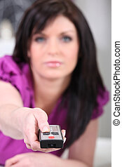 Brunette with a television remote control