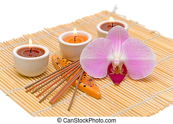 spa concept (candles, incense sticks and orchid) on a white...