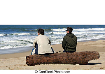Two men sitting at the beach and talking
