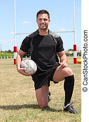 Man on rugby pitch kneeling with ball under arm