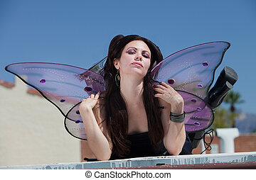 Fairy On Rooftop - Pretty Caucasian fairy pouts and sits on...