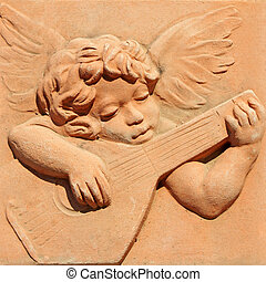 angel playing guitar in tuscan terracotta , Impruneta, Italy...