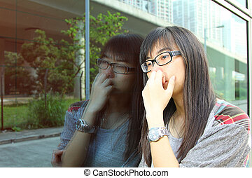 Asian woman with sad face, watching at glasses.