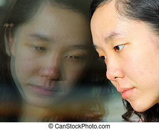 Asian girl with sad face, looking at the glass on train