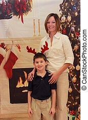 Mother and little boy in front of Christmas tree