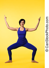 Young woman in blue doing yoga asana on yellow - young happy...
