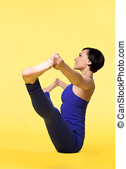 Woman in blue exercise yoga on yellow
