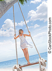 swing - View of nice tropical beach with girl on swing