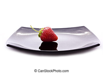 red strawberry on black plate isolated on white